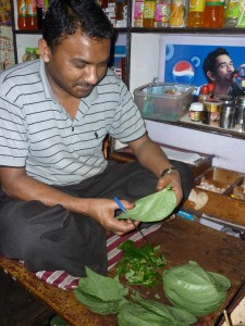 A man cutting Betel Nut leaves to make Paan